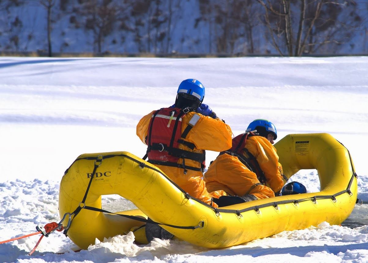 Two individuals in boat on snow-covered iced-over body of water for ice rescue