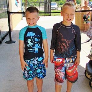 Young Boys Standing and Smiling Before Enjoying the Aquatic Center